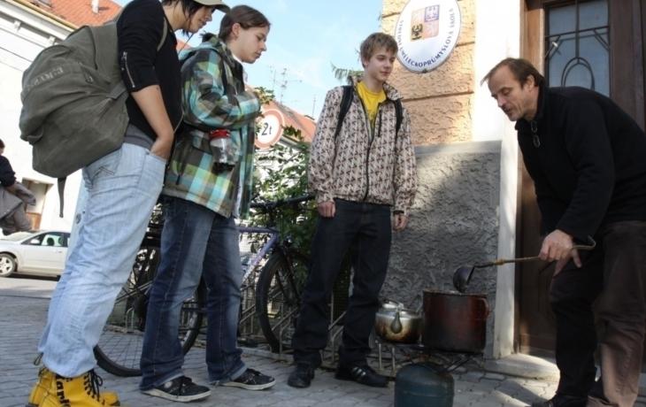 Sochař ohřívá vosk na ulici